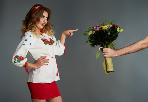 Happy Ukrainian woman receiving a bouquet of flowers from a man