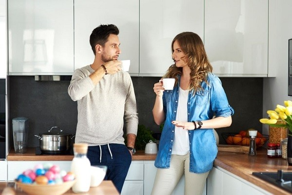 man and woman drinking coffee making eye contact