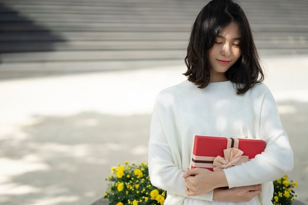 asian woman holding a red gift from a date