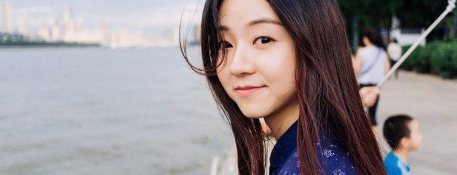 beautiful asian woman sitting near the shore